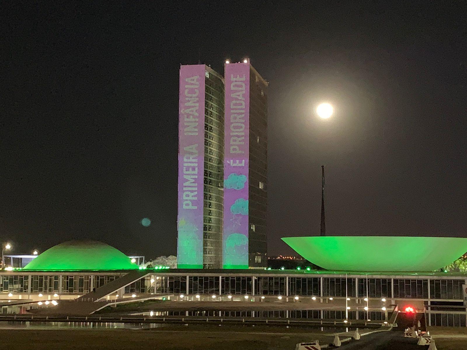 Prédio do Congresso Nacional está iluminado com as cores da Primeira Infância